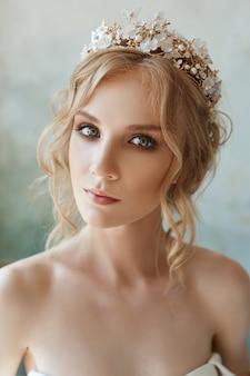 Dziewczyna w eleganckiej długiej sukni siedzi na podłodze. biała suknia ślubna na ciele panny młodej. piękna lekka sukienka z długim dołem, portret kruchej delikatnej dziewczyny przed ceremonią ślubną