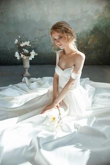 Dziewczyna w eleganckiej długiej sukni siedzi na podłodze