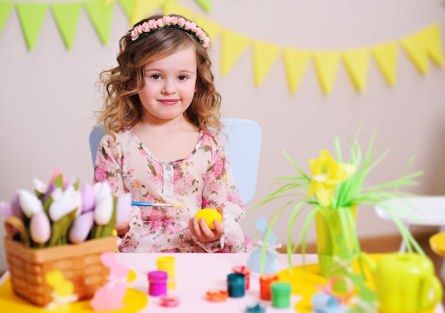 Dziewczyna w eleganckiej sukience maluje jajko siedzące przy stole z dekoracją wielkanocną