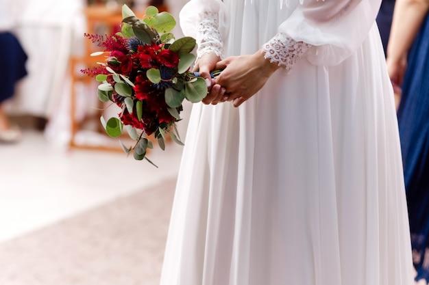 Dziewczyna w eleganckiej sukni stoi i trzyma bukiet ręcznie pastelowych kwiatów i zieleni ze wstążką w przyrodzie. panna młoda trzyma bukiet ślubny