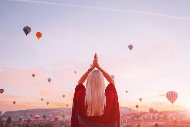 Dziewczyna w etnicznych ubraniach o świcie oglądająca lot wiele balonów lata nad doliną miłości