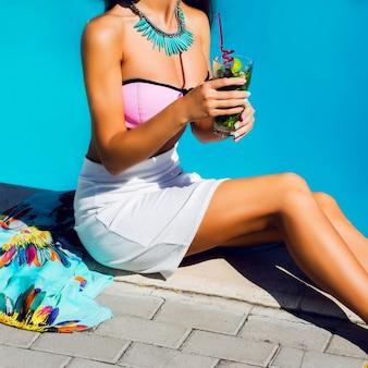 Dziewczyna w fajnych okularach przeciwsłonecznych, modnym różowym kapeluszu i jasnych egzotycznych akcesoriach pozuje i cieszy się imprezą przy basenie w luksusowej willi.