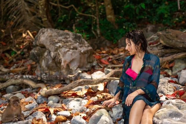 Dziewczyna w fajnym kostiumie kąpielowym i pareo rozmawia z małpami na tropikalnej plaży małp.