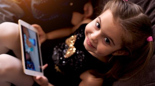 Dziewczyna w fantazyjny strój umiejscowienia na kanapie, patrząc na kamery