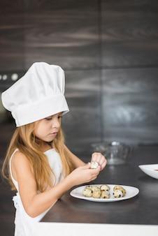 Dziewczyna w fartuch i szef kuchni kapelusz obieranie przepiórki jaj powłoki