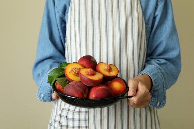 Dziewczyna w fartuchu trzyma miskę z dojrzałymi owocami brzoskwini