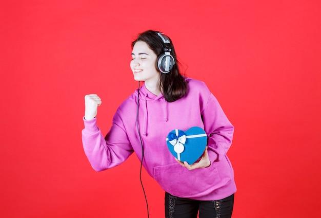 Dziewczyna w fioletowej koszuli pokazuje swoją moc, przechylając się na prawy bok i trzymając pudełko