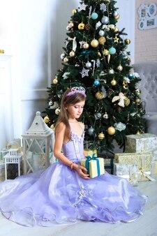 Dziewczyna w fioletowej sukience trzymająca prezent w pobliżu choinki