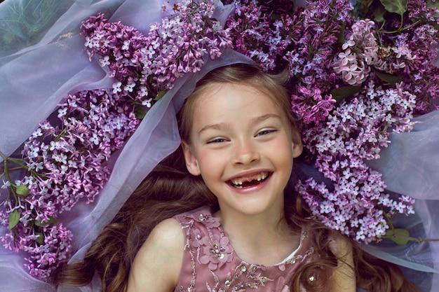 Dziewczyna w fioletowej sukience w kwiaty leży wśród kwiatów bzu