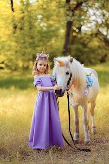Dziewczyna w fioletowej sukience z wieńcem jednorożca we włosach, przytulanie białego jednorożca