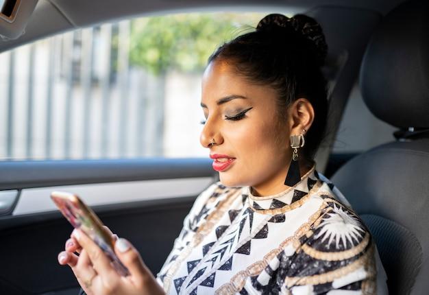 Dziewczyna w foteliku samochodowym rozmawia przez telefon