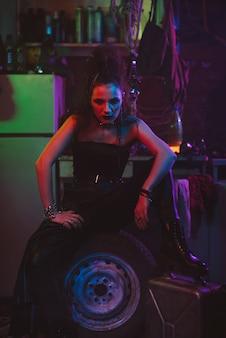Dziewczyna w futurystycznym cyberpunkowym stroju z neonowym oświetleniem. koncepcja przyszłej postapokalipsy