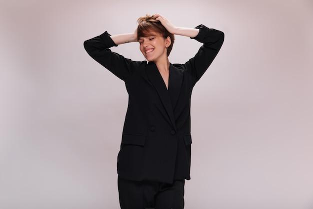 Dziewczyna w garniturze, zabawy na na białym tle. szczęśliwa pani w czarnym garniturze śmieje się na białym tle. krótkowłosa kobieta w ciemnej kurtce uśmiecha się