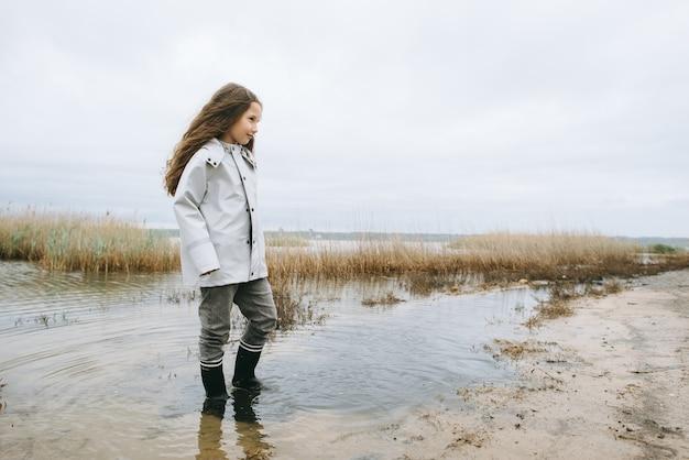 Dziewczyna w gumowych butach ma zabawę w pobliżu jeziora