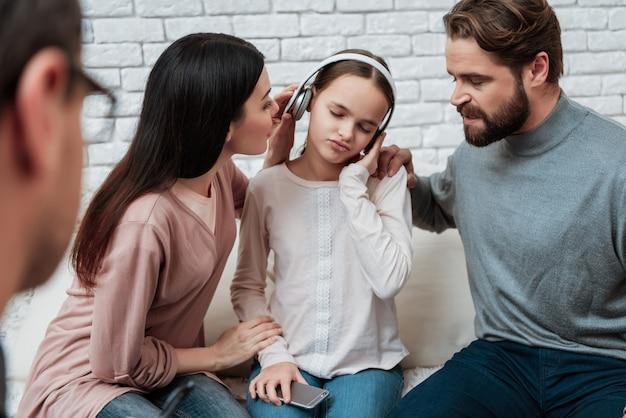 Dziewczyna w hełmofonach ignoruje rodziców w terapii