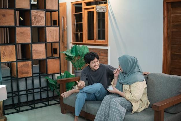 Dziewczyna w hidżabie i azjatycki chłopiec rozmawiają w salonie, trzymając kubek, siedząc na drewnianym krześle