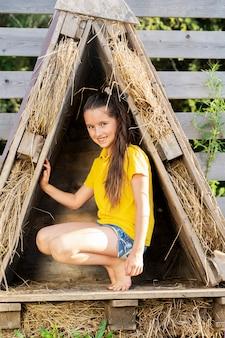 Dziewczyna w jasnożółtej koszulce siedzi w domu