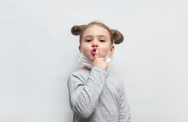 Dziewczyna w jednorazowej masce w górę jej palca na lekkim tle.