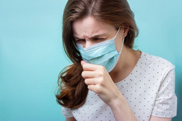 Dziewczyna w jednorazowej medycznej masce i szpitalu odziewa kaszle lub kicha na błękitnym odosobnionym tle. covid-19