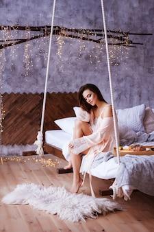 Dziewczyna w jej sypialni. piękne wnętrze. wiszące łóżko