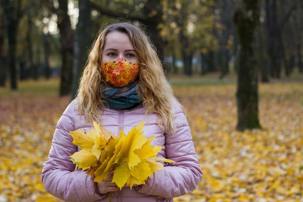 Dziewczyna w jesiennym parku z liściem klonu w dłoniach na tle parku