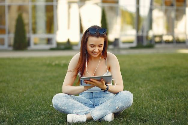 Dziewczyna w kampusie uniwersyteckim za pomocą tabletu