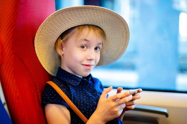 Dziewczyna w kapeluszu bawić się z telefonem komórkowym w autobusie