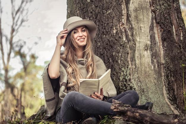 Dziewczyna w kapeluszu czyta książkę w lesie jesienią