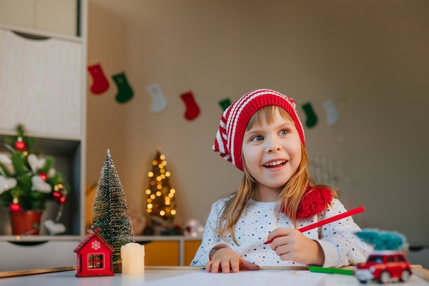 Dziewczyna W Kapeluszu Gnome Pisze List Do świętego Mikołaja Przy Stole W Pokoju Dziecięcym Premium Zdjęcia