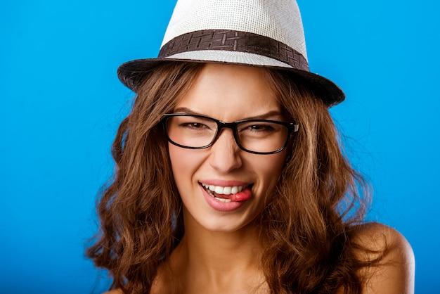 Dziewczyna w kapeluszu gryzie język