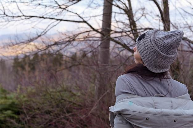 Dziewczyna w kapeluszu i kurtce stoi na panoramie w lesie, niebo jest drzewem. pojęcie turystyki i podróży. skopiuj miejsce
