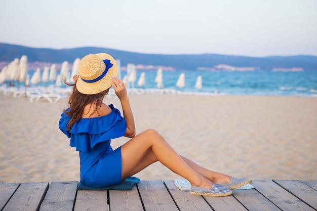 Dziewczyna w kapeluszu i niebieskiej sukience siedzi na piaszczystej plaży, piknik