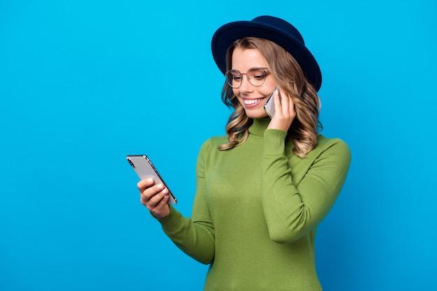 Dziewczyna w kapeluszu i okularach mówi przez telefon