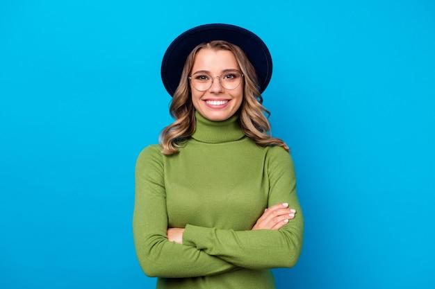Dziewczyna w kapeluszu i okularach na niebieskim tle