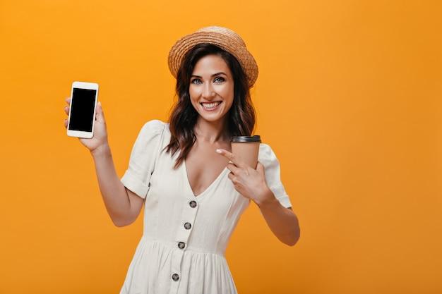 Dziewczyna w kapeluszu i sukni pokazuje na smartfonie i trzyma szklankę herbaty