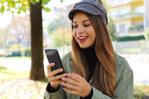 Dziewczyna w kapeluszu i szyi polo, czytając dobre wieści na świeżym powietrzu inteligentny telefon