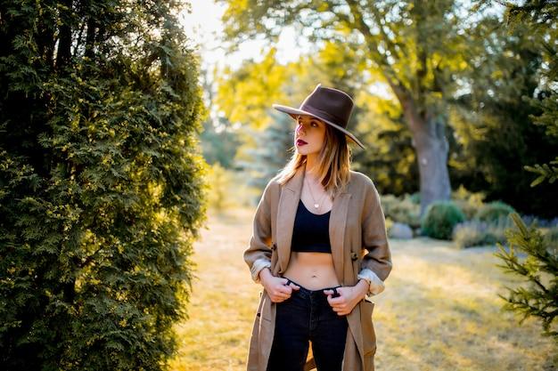 Dziewczyna w kapeluszu i ubraniach w wiejskim ogródzie w zmierzchu czasie