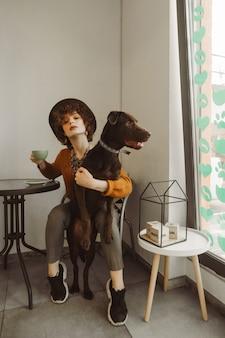 Dziewczyna w kapeluszu iz kręconymi włosami siedzi w kawiarni przy filiżance kawy i przytula psa