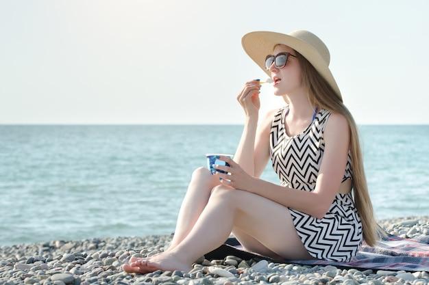 Dziewczyna w kapeluszu jeść lody na plaży. słoneczny dzień