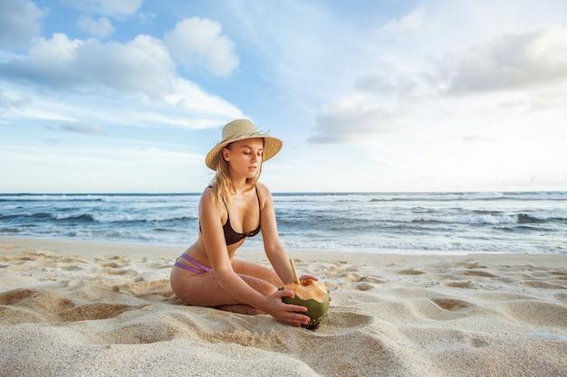 Dziewczyna w kapeluszu na plaży trzyma kokosa