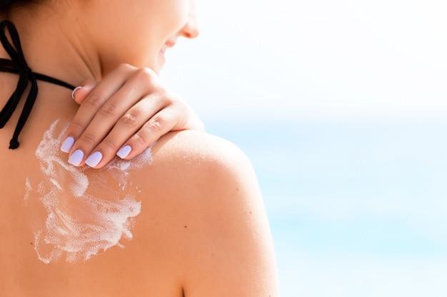 Dziewczyna w kapeluszu nakłada krem przeciwsłoneczny na plecy, aby chronić skórę