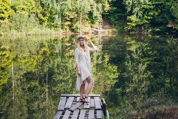 Dziewczyna w kapeluszu odpoczywa na jesieni jeziorze na moscie