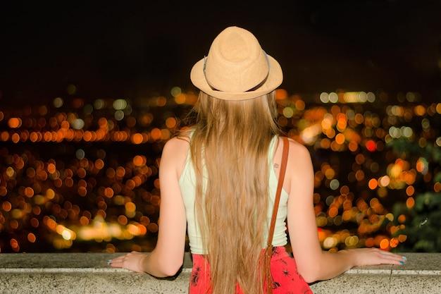 Dziewczyna w kapeluszu podziwia nocne miasto. widok z tyłu