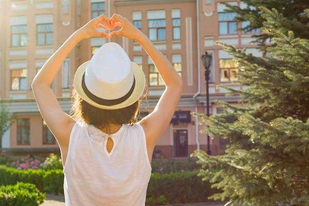 Dziewczyna w kapeluszu pokazuje serce