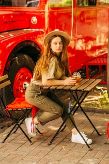 Dziewczyna w kapeluszu przy stole pije capo orange