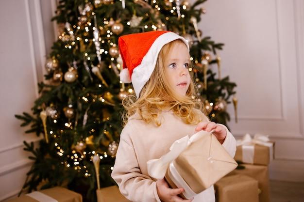 Dziewczyna w kapeluszu santa z prezentem na tle choinki. dziecko z prezentem świątecznym w domu.