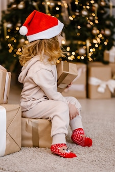 Dziewczyna w kapeluszu santa z prezentem na tle choinki.