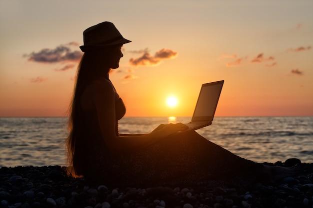 Dziewczyna w kapeluszu siedzi i pracuje na swoim laptopie na tle morza o zachodzie słońca