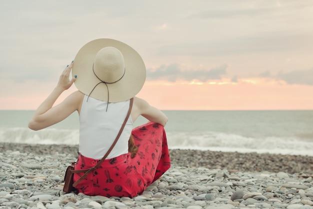 Dziewczyna w kapeluszu siedzi na kamienistej plaży. widok z tyłu. czas zachodu słońca