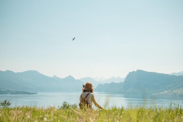 Dziewczyna w kapeluszu siedzi na zielonym trawniku w pobliżu jeziora